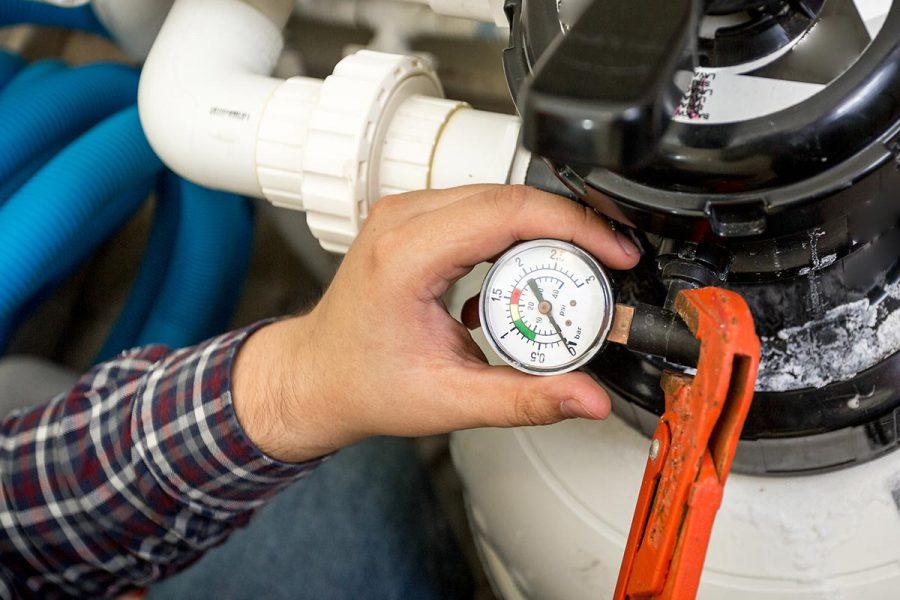 Closeup shot of plumber checking manometer on big hydraulic pump